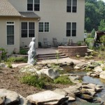 Erney Landscaping Backyard residential landscaping with pond and rocks