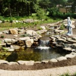 Erney Landscaping rock waterfall with three levels running into large pond